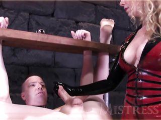 Госпожа в латексе зажимает яйца рабу и жестко дрочит член двумя руками
