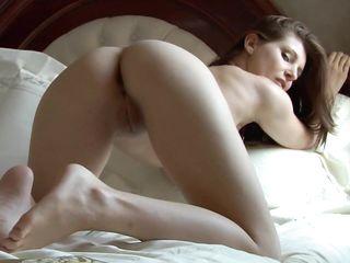 Молодая девушка с очень красивой грудью позирует голой на кровати м соблазняет сексуальностью
