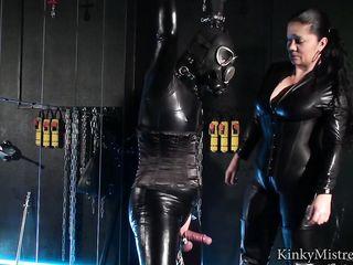 Зрелая женщина в кожаном костюме усердно дрочит вялый пенис рабу в черной униформе