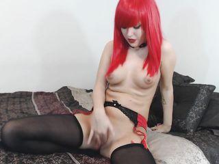 Девушка в красном парике ласкает рукой свою гладкую письку, пока оргазм не настигает ее