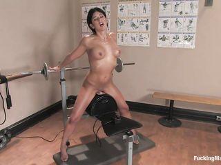 В спортзале девушка сидит на мощном вибраторе