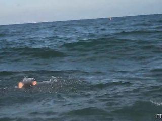 Голая девушка купается в море и веселится на пляже